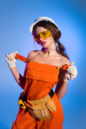 seductive girl in overalls uniform and safety helmet, isolated on blue Imagens