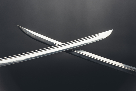 close-up shot of crossed katana blades on black