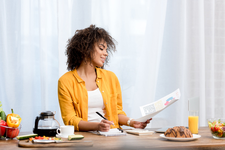 attractive african american woman working at home during breakfast Stock Photo