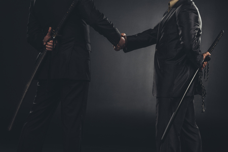 cropped shot of yakuza members shaking hands with katanas behind back isolated on black