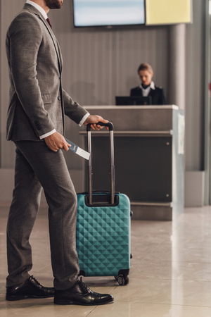 rear view of businessman with suitcase in front of airport check in counter Stockfoto