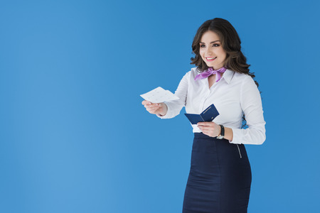 attractive stewardess giving tickets isolated on blue