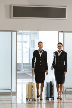 attractive young stewardesses at departure area of airport with suitcases