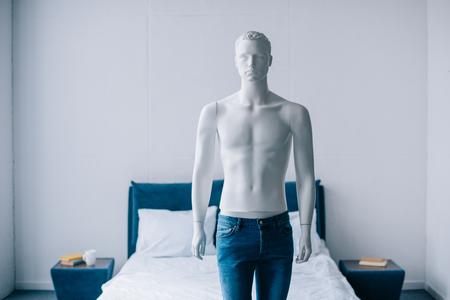 Nahaufnahme einer Laienpuppe in Jeans im Schlafzimmer