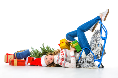 beautiful girl in santa hat lying with sledge, presents and christmas tree, isolated on white
