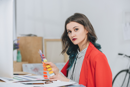 Attractive young girl working with palette by working table with computer