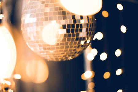 hermosa bola de discoteca con guirnalda dorada sobre negro Foto de archivo