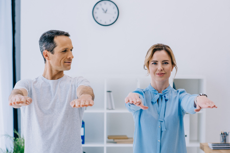 happy beautiful businesswoman doing exercise with trainer at office Stock Photo