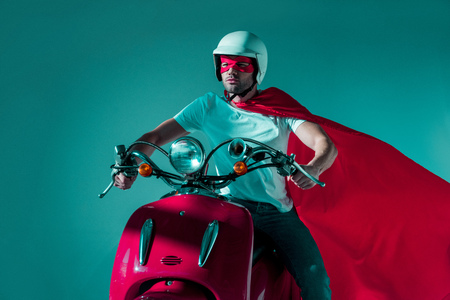 portrait of man in protective helmet, superhero mask and cape riding red scooter