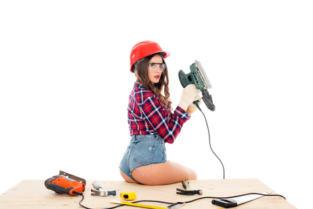 sexy girl in hardhat posing with grind tool on wooden table with tools, isolated on white