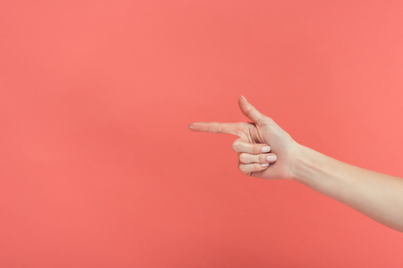 cropped view of female hand pointing isolated on red