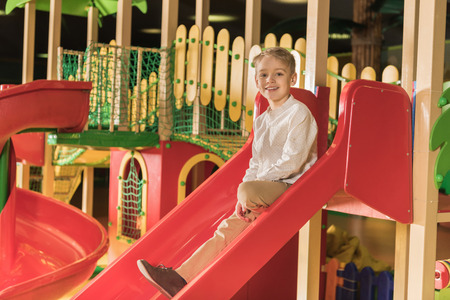 cute little boy smiling at camera while playing on slide at indoor play center