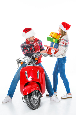 couple in santa hats with gift boxes on red scooter, isolated on white Stock Photo