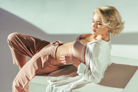 bella giovane donna sensuale in reggiseno, camicia e pantaloni rosa che si trovano nello studio