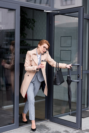 businesswoman with coffee to go talking on smartphone exiting business center