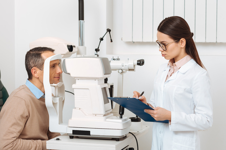 side view of patient getting eye examination in slit lamp in clinic Stok Fotoğraf