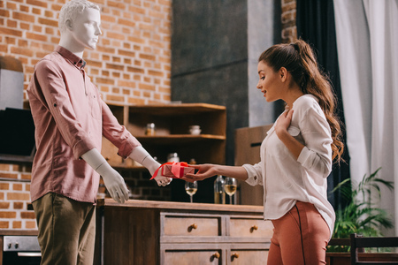 woman pretending to except gift from mannikin, loneliness and perfect man dream concept Stock fotó