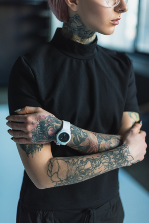 cropped shot of young tattooed businesswoman standing with crossed arms Stock Photo