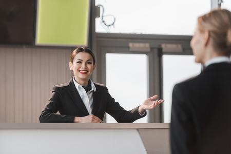 Recepcionista del aeropuerto atractivo sonriente hablando con el cliente