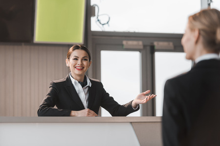smiling attractive airport receptionist talking to client Banque d'images - 114327787