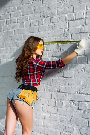 sexy girl with tool belt measuring white brick wall