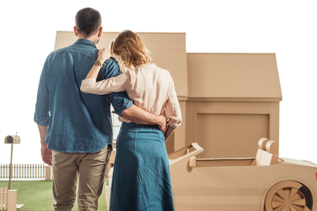 rear view of couple embracing in front of cardboard house and car isolated on white