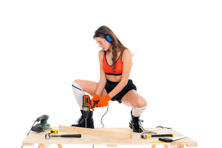 beautiful girl in protective headphones working with electric drill at wooden table with tools, isolated on white Imagens
