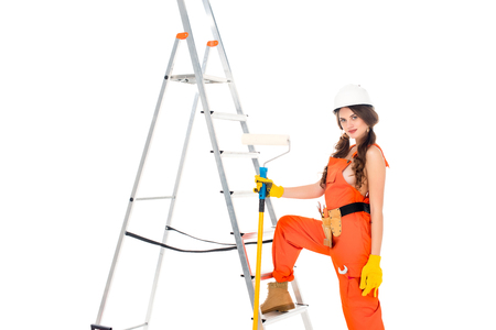 beautiful workwoman in uniform holding painting roller near ladder, isolated on white Banque d'images