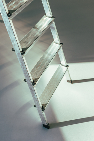 close-up view of metal stepladder in studio on grey