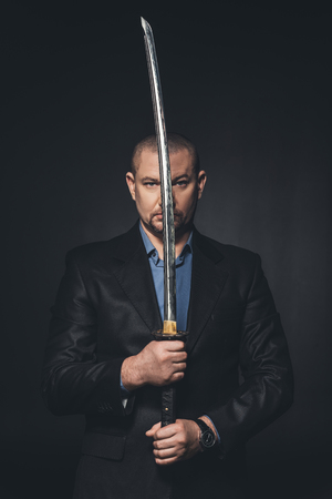 mature man in suit holding japanese katana sword in front of his face isolated on black