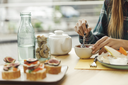 cropped shot of girl drinking tea while having breakfast Stock Photo