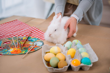 woman with white rabbit on table with colorful easter eggs