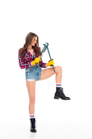 beautiful sexy girl posing with adjustable wrench, isolated on white Banque d'images - 114327741