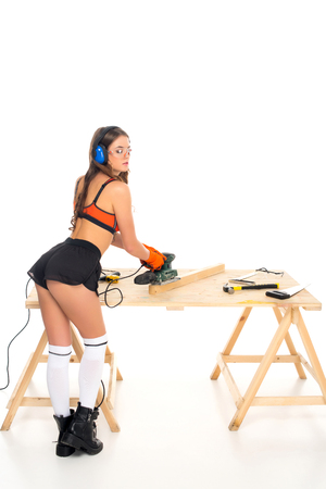 sexy girl in protective headphones working with grind tool on wooden table with tools, isolated on white