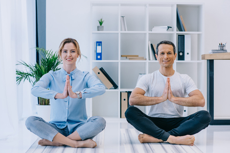 businesswoman with her trainer practicing yoga in lotus pose at office