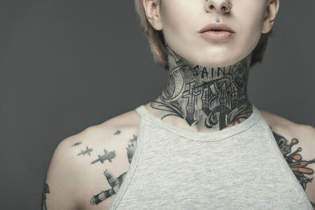 cropped view of attractive tattooed girl, isolated on grey