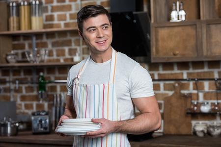 smiling handsome man in apron holding plates at kitchen Banco de Imagens