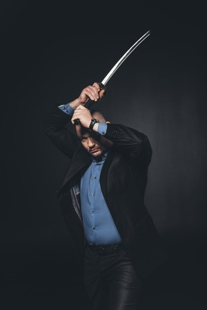 mature man in suit making hit with katana sword on black