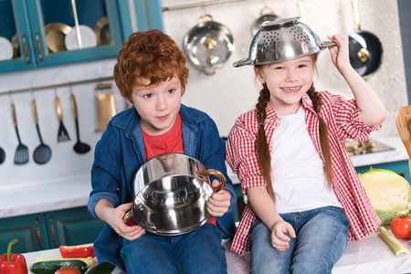 adorable children having fun with utensils in kitchen