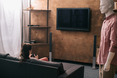 back view of woman playing video game and mannikin aside at home, one way love concept