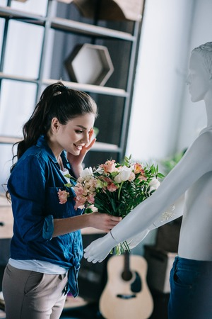 young woman pretending to receive flowers from layman doll, perfect relationship dream concept Banco de Imagens