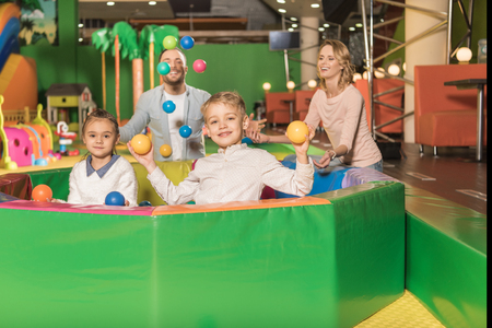 happy parents looking at cute little kids smiling at camera and playing with colorful balls in game center Stock fotó - 114328031