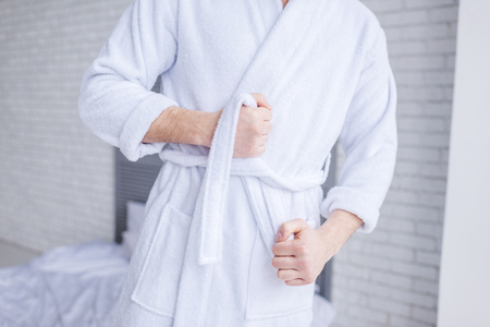mid section of man wearing bathrobe at home Archivio Fotografico
