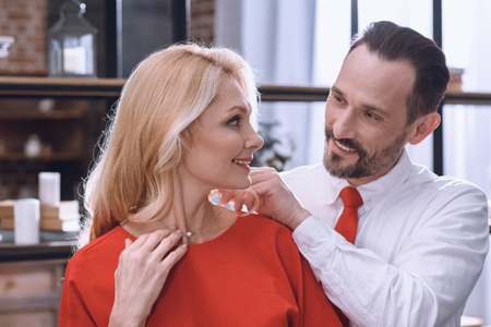 smiling husband wearing necklace on wife neck, st valentines day concept Stock Photo