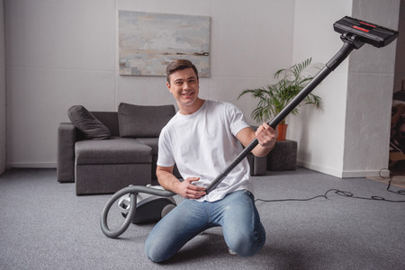 handsome man having fun with vacuum cleaner in living room and looking at camera
