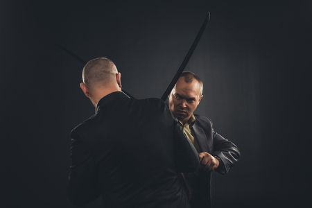 businessmen fighting with katana swords isolated on black