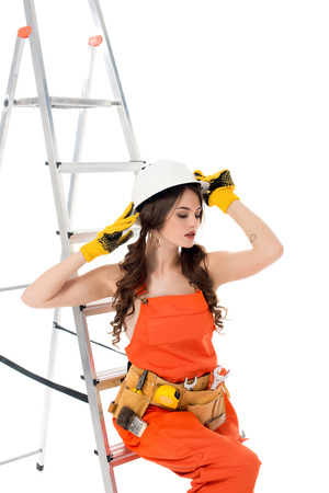 brunette workwoman in overalls and safety helmet posing near ladder, isolated on white Stockfoto