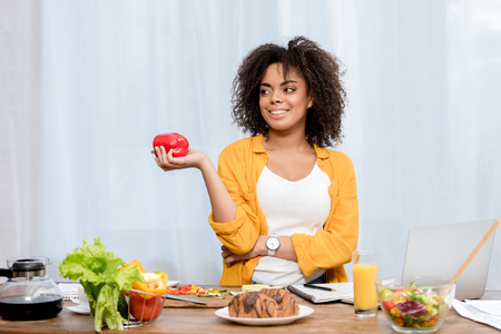 beautiful young woman with various food and working supplies on table working at home