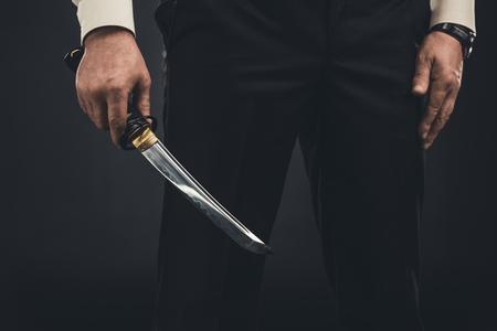 cropped shot of yakuza member with tanto knife