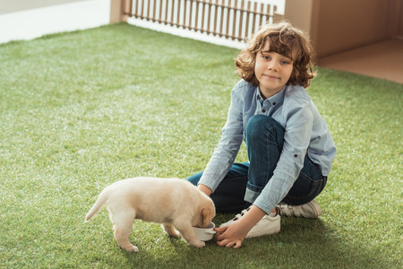 little kid feeding his labrador puppy on grass